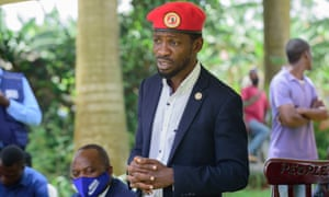 The Ugandan opposition leader Bobi Wine, wearing a dark blue suite and red beret, stands with with his hands clasped