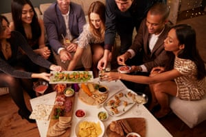 Group of friends enjoying drinks and snacks at a party