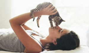 A young girl holding a kitten in the air and giving it kisses