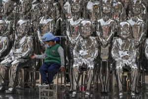 A child tries to hold a statue's hand as he sits in an art installation at a shopping mall