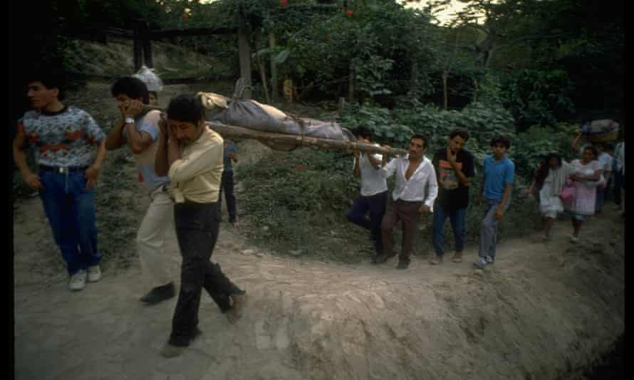 Relatives of 15 family members massacred by civil war combatants, bearing bodies on stretchers.