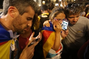 People with Catalan independence flags strain to hear a 9pm statement by the regional president, Carles Puigdemont, on their smartphones