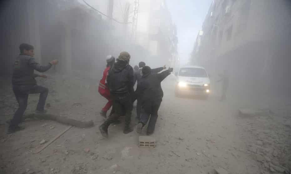 Residents and a member of the Syrian Red Crescent carry an injured man, after an air-strike in eastern Ghouta.