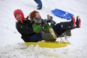 Children enjoy a day off school with some sledging at The Great Field in Poundbury, Dorset