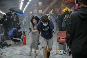 Protesters run for cover after riot police fired tear gas towards the bridge they were climbing down to the road below, to escape from Hong Kong Polytechnic University campus and from police