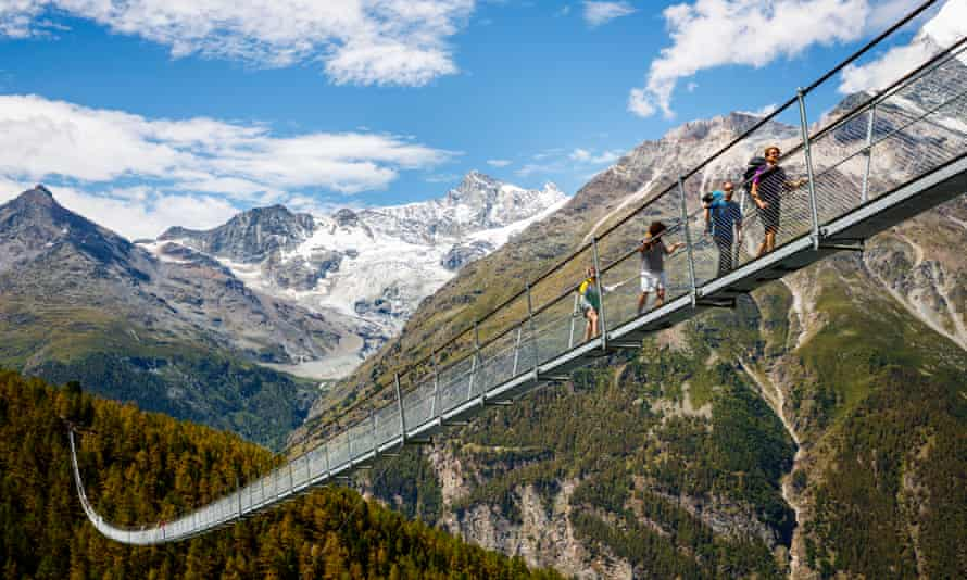 Hikers make their way across the newly opened suspension bridge in Randa, Switzerland.