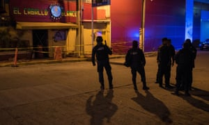 Police officers keep watch outside the Caballo Blanco following a deadly arson attack, in Coatzacoalcos, Mexico, on 28 August. Andrés Manuel López Obrador promised an inquiry would 'get to the bottom' of it.