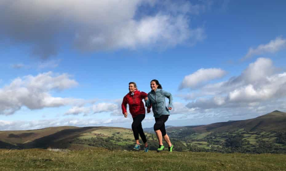 Ruth Pickvance and Ellie Ross running side by side on a hillside, blue sky with fluffy clouds behind