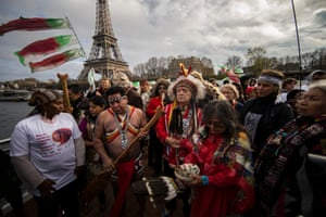 Indigenous representatives from around the world engage in a joint prayer session on board a boat in Paris