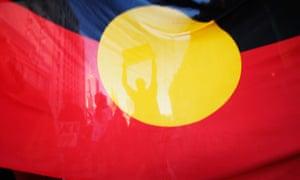 People's shadows behind an Aboriginal flag