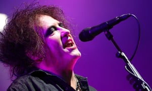 Robert Smith of the Cure singing into microphone