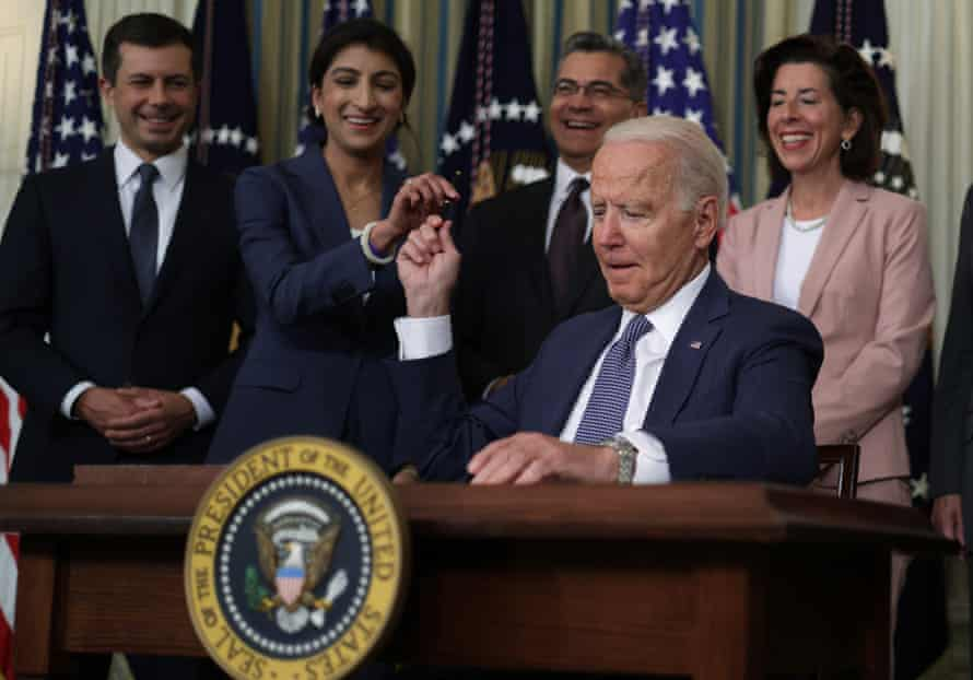 Joe Biden hands a signing pen to Lina Khan on 9 July after signing an executive order to promote competition in the American economy.