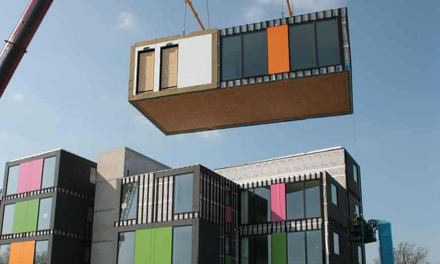 A modular home being lifted by a crane in London