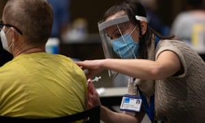 Virgina Mason pharmacist Amanda Locke gives a dose of the Pfizer Covid-19 vaccine at the Amazon Meeting Center in downtown Seattle, Washington on 24 January, 2021.
