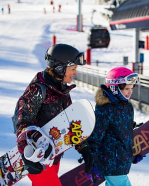 Mother and daughter carry their snowboards to the ski lift