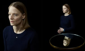 Jodie Foster in double, with the one behind standing next to a glass reflecting her image. The background is black