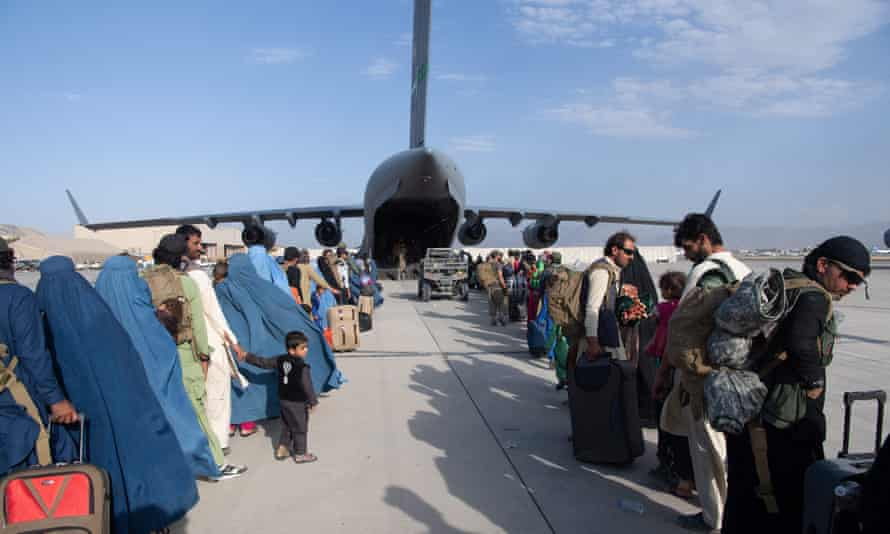 People wait to board a US evacuation plane at Kabul airport