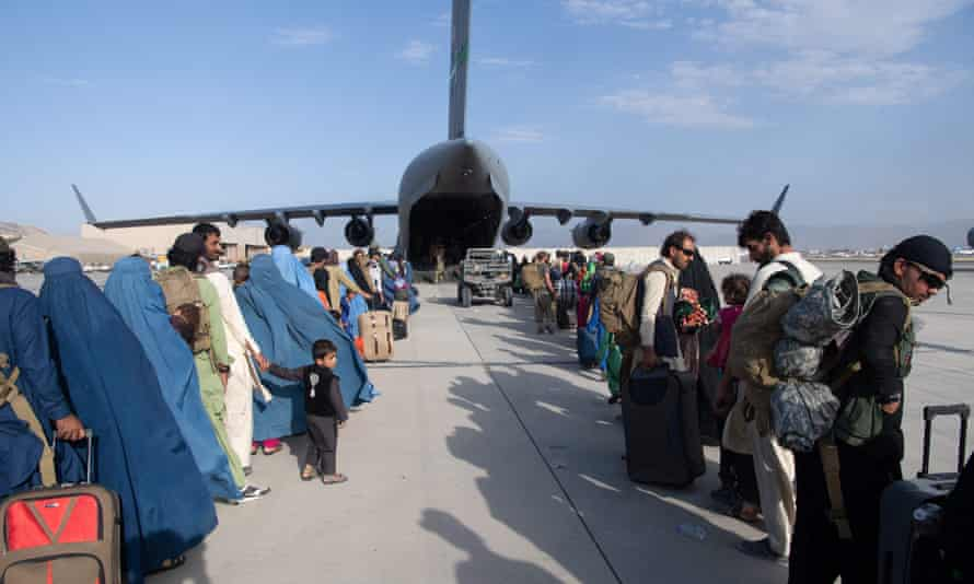 Evacuees wait to board a US air force plane at Kabul airport, 25 August.