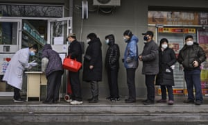 Chinese residents line up to get a free protective mask at a local pharmacy in Beijing.