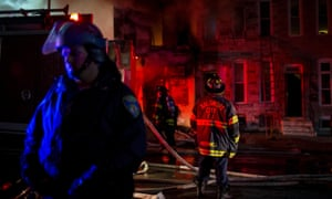 A police officer stands nearby as firefighters attack a fire in a convenience store.