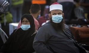 Warga Palestina yang mengenakan masker wajah duduk di samping barang bawaan mereka saat mereka menunggu untuk menyeberang ke perbatasan Rafah dengan Mesir, di Jalur Gaza selatan, Minggu, 27 September 2020.