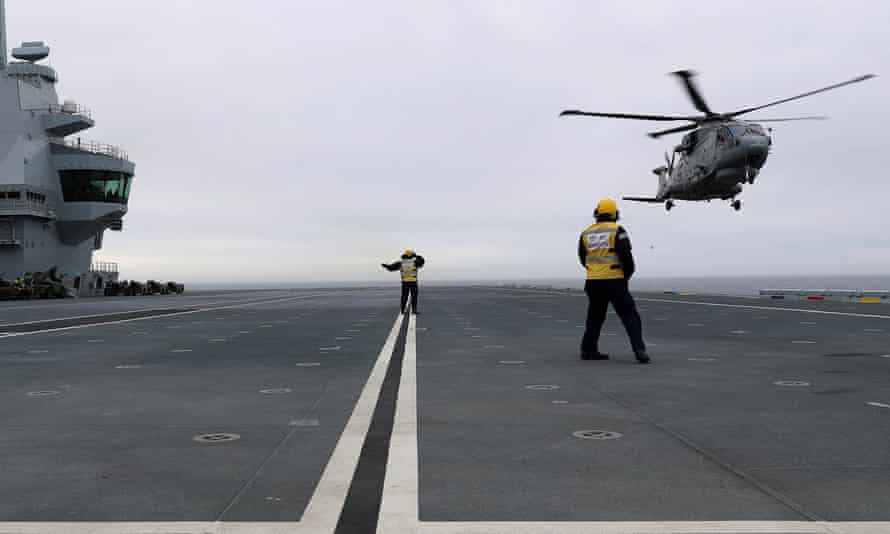 A Merlin helicopter makes the first ever deck landing on the Royal Navy aircraft carrier HMS Queen Elizabeth.