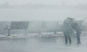 People struggle against the wind as waves crash against the sea wall at Southsea, Portsmouth