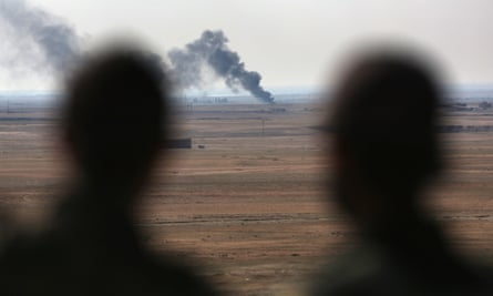 Kurdish forces overlook a burning oil well in Rojava, northern Syria.