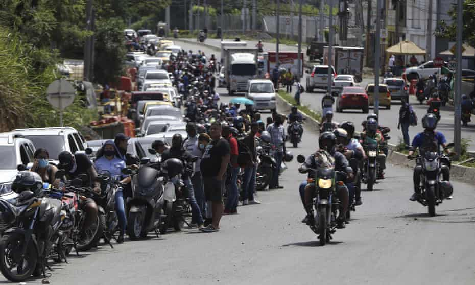 Drivers and motorcyclists wait their turn to fill up at a gas station in Cali.