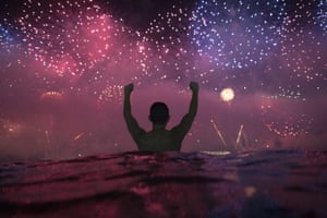 A man watches the fireworks exploding over Copacabana Beach in Rio de Janeiro, Brazil.