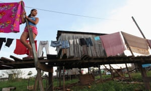 A resident stands outside her house in Altamira, Brazil. Houses in the neighbourhood are built on stilts to protect against seasonal rains, but now, because of the dam, they are prone to flooding throughout the year.