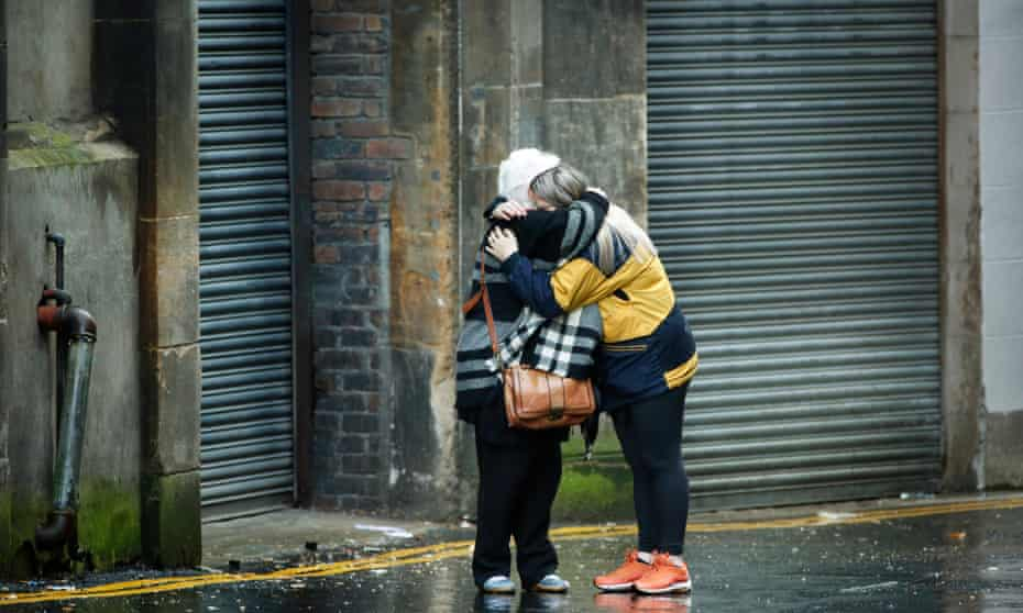 Two people hug in Mitchell Street Glasgow.