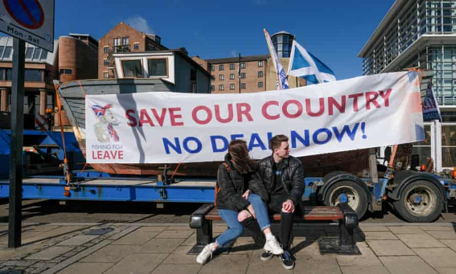 A couple sit on a bench as a 30ft fishing boat on a lorry drives past as part of the 'Fishing for Leave' protest on the River Tyne in Newcastle