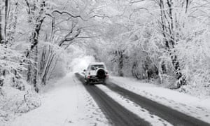 Driving through a snow covered winter wonderland tunnel along country lane