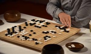 Fan Hui makes a move against AlphaGo in DeepMind's HQ in King's Cross