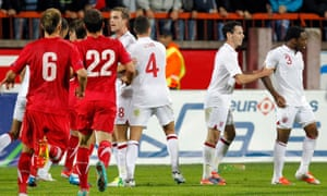 Danny Rose (right) is shepherded away by Adam Smith  while Jordan Henderson and Jason Lowe confront Serbia Under-21s players after a 2012 game marred by monkey chants and stones thrown at Rose