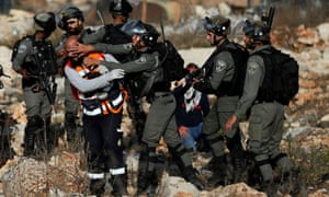 A Palestinian medic is pushed back by an Israeli border policeman as he tries to help a wounded demonstrator during an anti-Israel protest near the Jewish settlement of Beit El in the Israeli-occupied West Bank on Monday.
