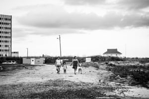 Mothers and daughters walk through the detritus of failed development to get to the water's edge. August 2016
