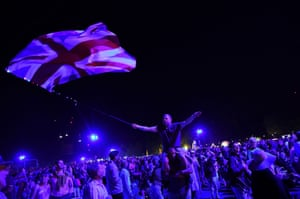Revellers wave British flags as they enjoy the Last Night of the Proms celebration in Hyde Park, London