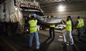 Sanitation workers clear debris left behind by people evicted from an encampment.