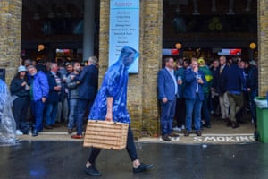 A spectator carries a hamper past sheltering spectators as rain delays the start of the first day of the second Ashes Test.at Lord's.
