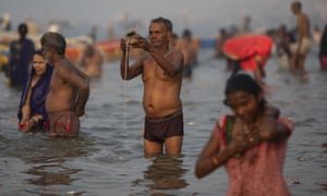 A pilgrim prays at Sangam, the confluence of the rivers Ganges and Yamuna.