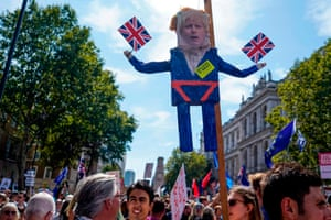 Protesters carry an effigy of the PM at a demonstration against the move to suspend parliament