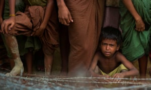 A young Rohingya refugee sits behind barbed wire in Maungdaw, Myanmar