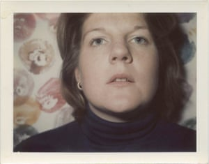 A self-portrait Polaroid photograph by Brigid Berlin, with a background of her Tit Prints, made by dipping her breasts in paint and smearing them on to paper.