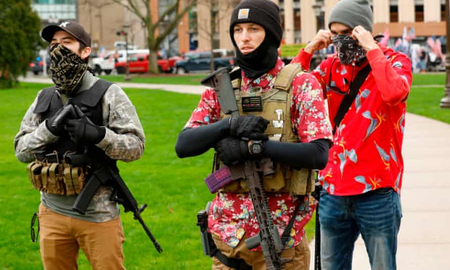 Armed protesters provide security for a protest demanding reopening in Lansing, Michigan, on 30 April. Members of the 'boogaloo' movement wear Hawaiian shirts paired with body armor and a military-style rifle.