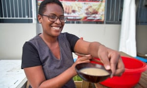 A woman enjoys a bowl of kava at the Kava Bure in Suva.