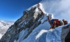 Queues of mountain climbers lining up to stand at the summit of Mount Everest