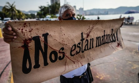 A Mexican journalist holds a placard that reads 'they are killing us' during a protest demanding protection after colleagues were threatened by organized crime, in Acapulco last month.