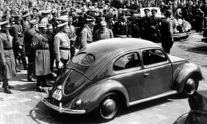 Adolf Hitler inspects the new 'People's Car' at a Wolfsburg factory in 1938. On Hitler's left is the car's designer, Dr Ferdinand Porsche.